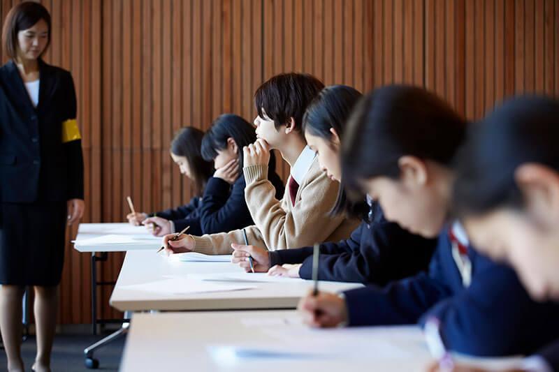試験監督と試験を受ける複数の学生