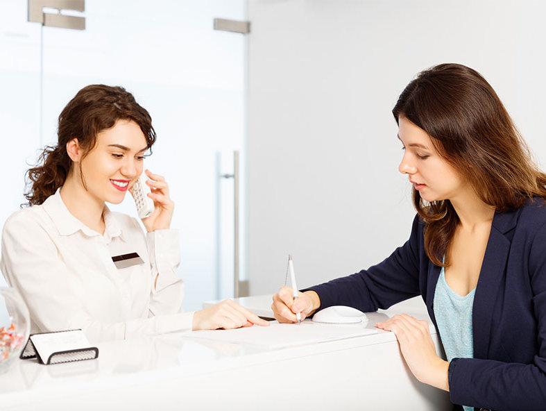 病院の受付で書類にサインする女性