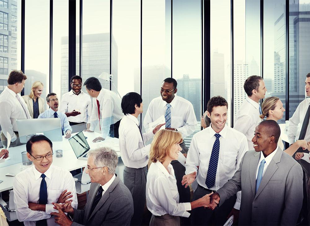 オフィス内で会話する複数のビジネスマン