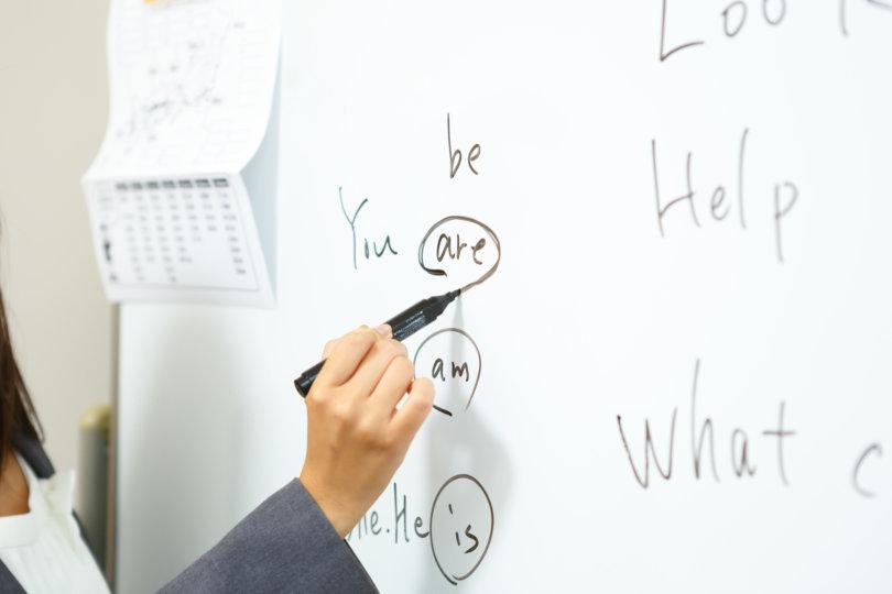 ホワイトボード上のbe動詞に○印を書いている様子