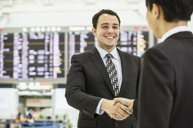 空港で握手を交わす二人の男性