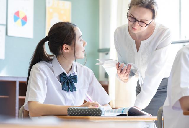 英語を教える女性とそれを聞く生徒