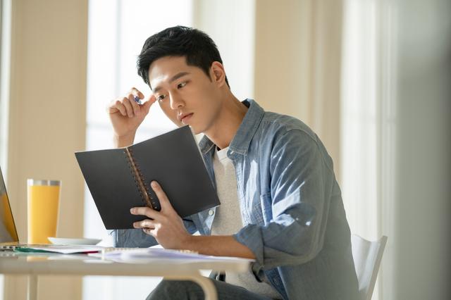 悩みながら英語の勉強をする男性