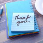 青いボールペンと手帳の上に「Thank you」と書かれたメモ