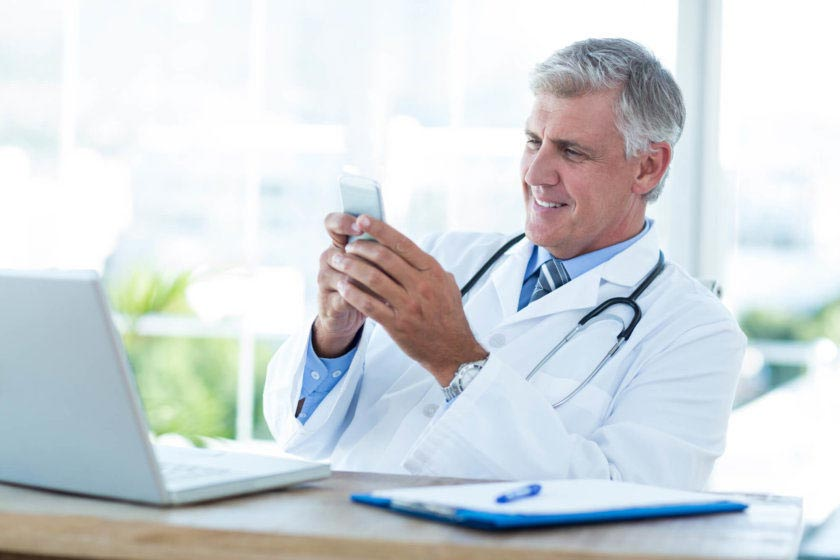 スマホでメールを確認するドクター